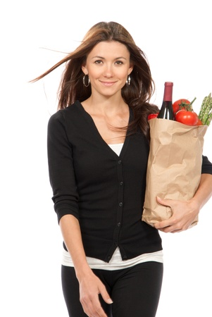 Pretty young woman holding a shopping bag full of vegetarian groceries, tomatos, salad, bottle of red wine, orange, papper isolated on white background  photo