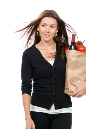 Happy young woman holding a supermarket paper shopping bag full of groceries, mango, salad, asparagus, radish, avocado, lemon, carrots, red wine on white background  Stock Photo - 9606887