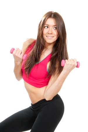 Fitness woman on diet standing sideways, holding pink dumbbells in hands and working out, showing muscular arms, abs, legs on a white background Stock Photo - 9606900