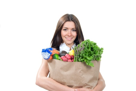 Happy young woman holding a supermarket shopping bag full of groceries, cucumbers, salad, asparagus, radish, avocado, lemon, carrots on white background photo