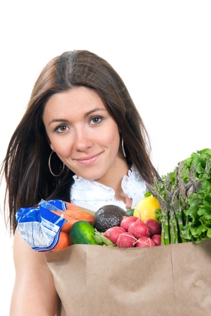 canned fruit: Happy young woman holding a supermarket shopping bag full of groceries, cucumbers, salad, asparagus, radish, avocado, lemon, carrots on white background  Stock Photo