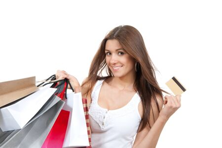 Pretty young woman with shopping bags, credit gift card in one hand buying presentsin supermarket, smiling and looking at the camera isolated on a white background  photo