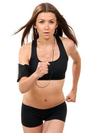 actief luisteren: Happy jonge fitness mooie slanke brunette sport vrouw joggen en hardlopen, luisteren naar muziek die op een witte achtergrond Stockfoto