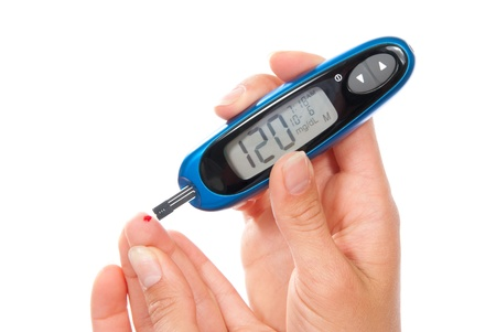 diabetic: Diabetes patient measuring glucose level blood test using ultra mini glucometer and small drop of blood from finger and test strips. Device show 120