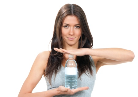 Sport fitness Woman in sportswear holding in hands drinking clear water in plastic advertising bottle isolated on a white background