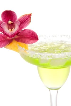 shaken: Margarita cocktail with beautiful orchid flower in chilled salt rimmed glass with tequila, orange syrup, fresh mint, pineapplel, crushed ice in cocktails glass isolated on white background