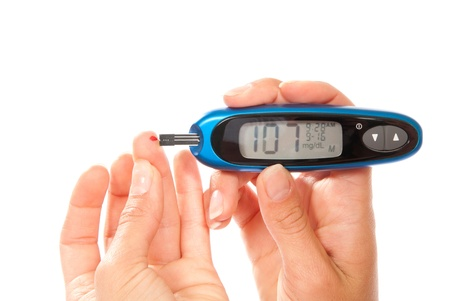 diabetic: diabetes patient Measuring glucose level blood using glucometer test isolated on a white background. Low blood sugar hypoglycemia