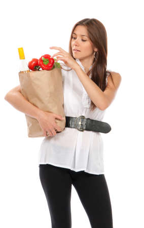 Young happy woman holding shopping paper bag full of vegetarian groceries, red pepper, salad, bottle of dry wine, mango isolated on white background