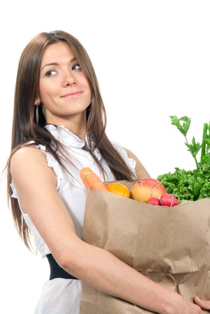 Happy young woman holding a shopping bag full of groceries, mango, salad, asparagus, radish, avocado, lemon, carrots on white background Stock Photo - 9837402