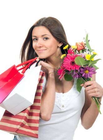 ecstatic: Beautiful ecstatic woman holding shopping bags, presents and bouquet of flowers a white background