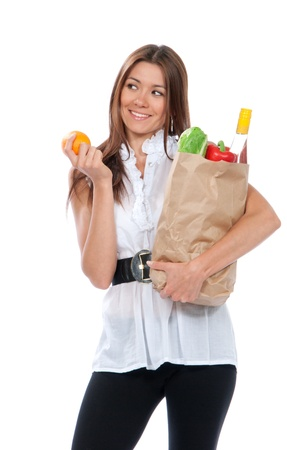 Happy young woman holding a shopping bag full of groceries, fresh salad, red pepper, bottle og wine and orange in hand isolated on white background  Stock Photo - 9837665