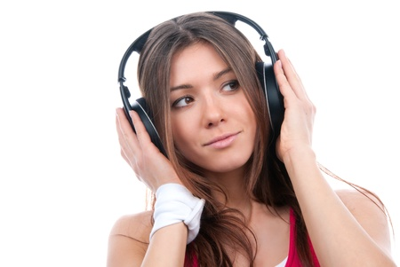 Attractive cheerful brunette woman listening and enjoying music in big headphones closeup portrait isolated on a white background  photo
