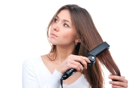 Young brunette woman using hair straighteners black flat iron to make new stylish hairstyle isolated on a white background  photo