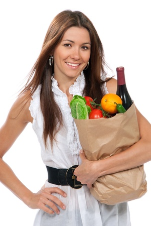 Happy young woman holding a paper shopping bag full of groceries salad, green pepper, tomatoes, orange, bottle of wine isolated on white background  Stock Photo - 9969076