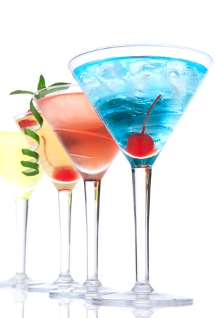 Martini alcohol cocktails in row  blue hawaiian, tequila sunrise, garnished with cherry, lime, mint in martinis cocktail glasses on a white background  photo
