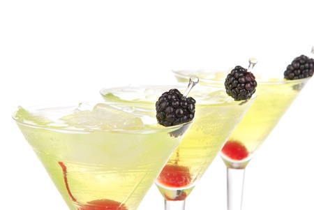Closeup yellow green martini cocktails row composition with alcohol, maraschino cherry, blackberry, vodka, curacao and crushed ice on a white background  photo