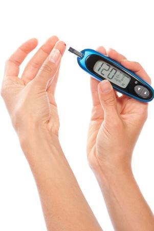 Afhankelijke Diabetes patiënt bloedglucose niveau bloedtest met behulp van ultra mini glucometer en kleine druppel bloed van vinger en teststrips geïsoleerd op een witte achtergrond meten