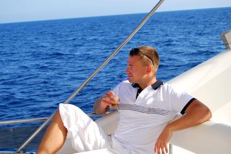 Jonge Zeeman ontspannen gelukkig op de vakantie jachtverhuur jacht en het drinken van koude frappe met een rust op de zomer boot over blauwe oceaan achtergrond