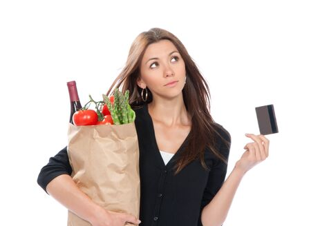 Pretty young woman holding a shopping bag full of vegetarian groceries in supermarket with tomatoes, asparagus, bottle of red wine and credit card isolated on white background  Stock Photo