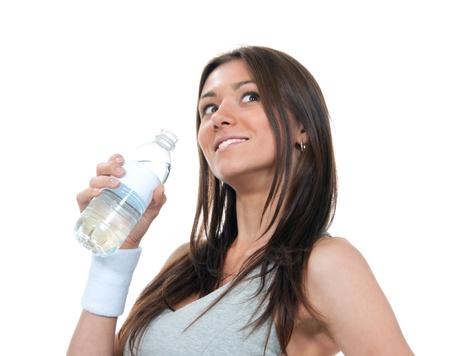 女の子は純粋なまだ飲料水栄養事実のボトルを保持します。女性の手に輝く鉱物を保持しているペットボトルの水、白い背景で隔離