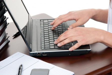 the author: Hands typing on the laptop computer keyboard in an office at a workplace isolated on a white background