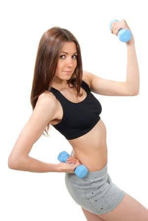 フィットネス女性インストラクター重量挙げ完璧なスポーツマン体型と abs 樹脂の重みにダンベル ジムでワークアウト、白い背景に分離 写真素材