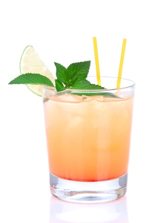 Alcohol tequila sunrise cocktail with crushed ice, green mint, yellow straws, lime in small glass isolated on white background