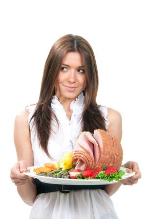 Vrouw wacht bord heerlijke hele gebakken honing gesneden ham, verse aardbeien, groente salade, wortelen, asperges, biologische citroenen voor het diner geïsoleerd op een witte achtergrond