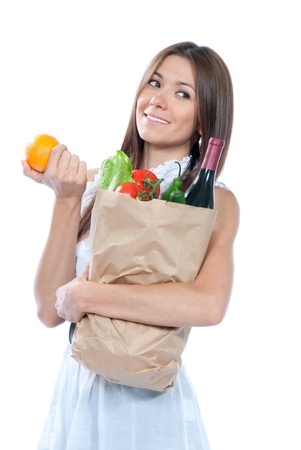 Happy young woman holding a paper shopping bag full of groceries, pepper, salad, asparagus, bottle of wine, tomatoes, orange, carrots on white background Stock Photo - 10266318