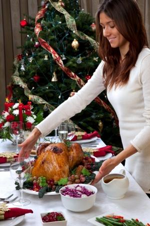 Gegarneerd Kerst geroosterde kalkoen in jonge mooie vrouw handen voorbereid voor de traditionele familie diner versierd met salade, fruit, groenten, wijn en champagne glazen op Kerstmis boom achtergrond