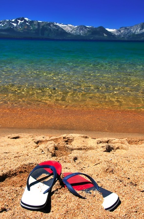 tahoe: Beautiful exotic beach for relax with snow mountains azure clear water and flipflops on sand. Focus on Flip-flops Stock Photo