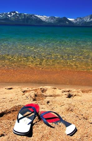 Mooie exotische strand om te ontspannen met sneeuw bergen azuurblauwe heldere water en de flipflops op zand. Focus op Flip-flops