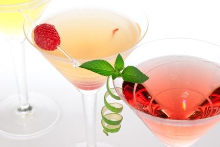 Martini alcohol cocktails in rij margarita, tequila sunrise, gegarneerd met kersen, limoen, mint in martini cocktail glazen Stockfoto