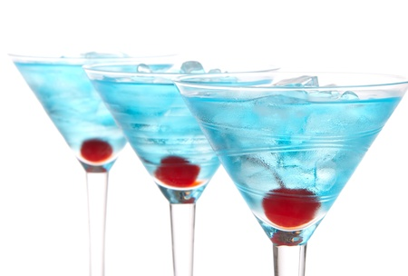 Blue martini cocktails row composition with alcohol, maraschino cherry, vodka, curacao and crushed ice on a white background