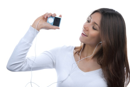 Young girl listening, enjoying music and holding cellular mp3 player in earphones on top of her head isolated on white background  photo