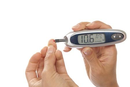 Afhankelijk eerste type diabetes patiënt het meten van glucose niveau bloedonderzoek met behulp van ultra mini glucometer en kleine druppel bloed uit de vinger en teststrips geïsoleerd op een witte achtergrond