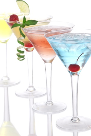 Martini alcohol cocktails in row blue hawaiian, tequila sunrise, garnished with cherry, lime, mint in martinis cocktail glasses on a white background