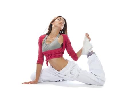 꽤 유연한 댄서 여자 반 감기에 앉아 흰색 배경에 스트레칭