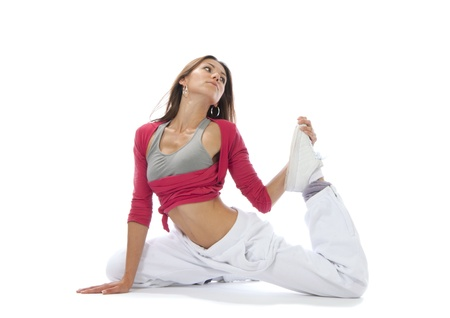Pretty flexible dancer woman sit on half twine and stretching on a white background