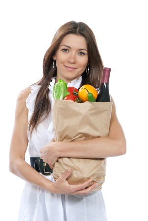 Happy young woman holding paper shopping bag full of groceries in supermarket, orange, salad, asparagus, bottle of red wine, tomatoes in hands on white background  Stock Photo - 10654197