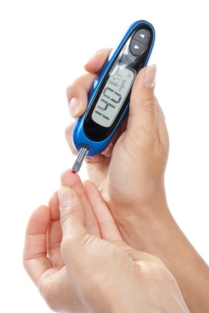 diabetes: Dependent first type Diabetes patient measuring glucose level blood test using ultra mini glucometer and small drop of blood from finger and test strips isolated on a white background