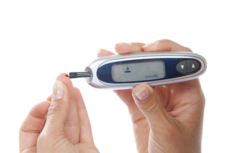 Diabetes patiënt het meten van glucose niveau bloedonderzoek met behulp van ultra mini glucometer en kleine druppel bloed uit de vinger en teststrips geïsoleerd op een witte achtergrond