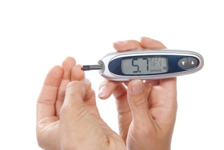 Diabetes patiënt meet glucose niveau bloedonderzoek met behulp van ultra mini glucometer en kleine druppel bloed uit de vinger en teststrips geïsoleerd op een witte achtergrond