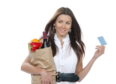 Young woman holding a shopping bag full of groceries and credit card in hands and smiling on a white background