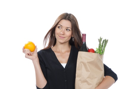Pretty young woman holding a shopping bag full of vegetarian groceries and orange in hand on a white background photo