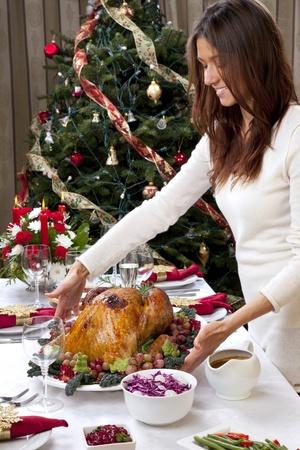 Vrouw met Gegarneerde kerst geroosterde kalkoen met de traditionele familiediner te vieren met salade, fruit, groenten, wijn en champagne glazen op kerst boom achtergrond Stockfoto