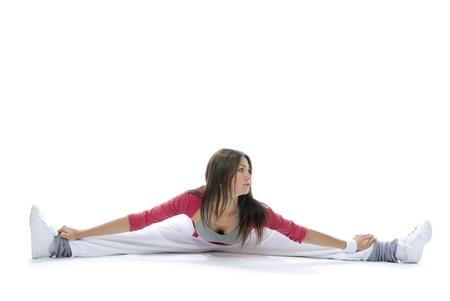 꽤 유연한 댄서 여자가 감기에 앉아 흰색 배경에 스트레칭