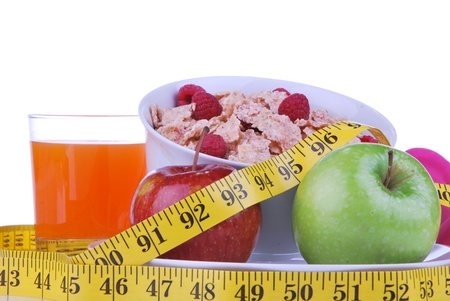 Diet weight loss food breakfast concept with tape measure natural green apple, corn healthy flakes with fresh raspberries and carrot juice  on a white background  photo