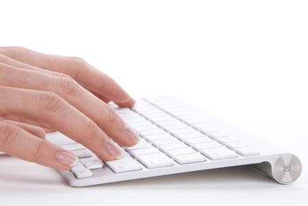 keyboard: Hands typing on the remote wireless computer keyboard in an office at a workplace isolated on a white background Stock Photo