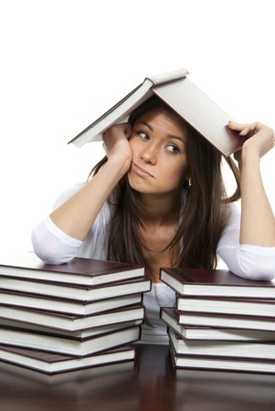 Girl tired of reading books studying school or college bored with the book on head, getting ready for college classes on a white background  photo